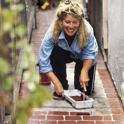 woman painting brick pattern on outdoor walkway