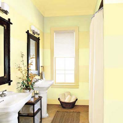 small bathroom painted with pale green and yellow stripes
