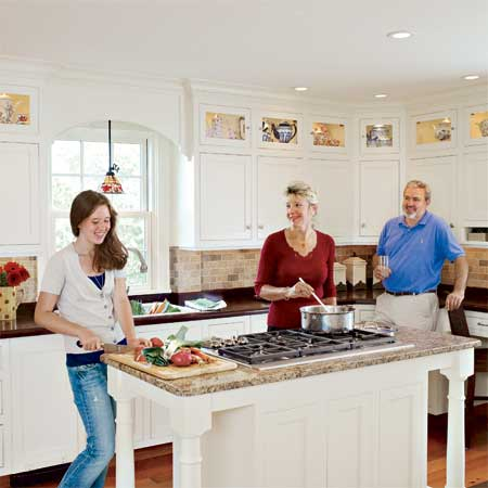 family enjoying their bright open kitchen with island in this remodeled greek revival