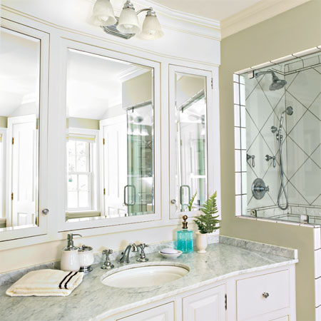 triptych mirror vanity hangs in the master bath of this remodeled greek revival