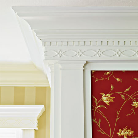 tapered pilasters topped with dentil molding and a double-fish motif over the fireplace in the master suite of this remodeled greek revival