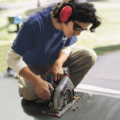 man using a circular saw to cut deck boards