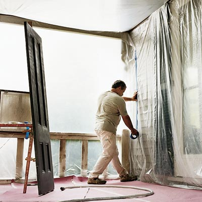 man installing plastic and drop cloths to prepare for spray painting