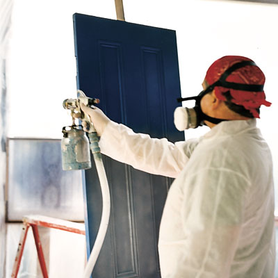 man spray painting door
