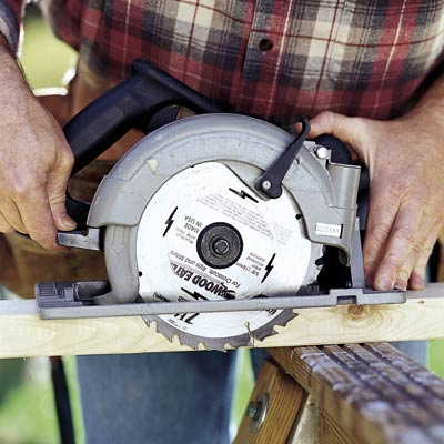 man using circular saw and setting blade depth