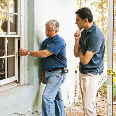 men checking exterior of window for lead paint