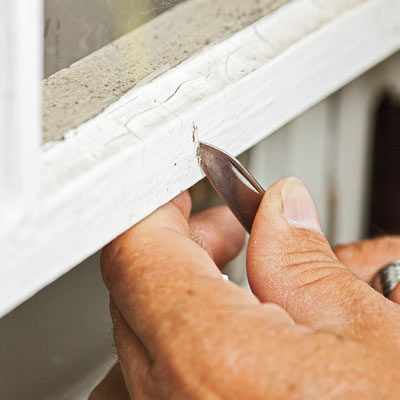hand cutting exterior paint to check for lead