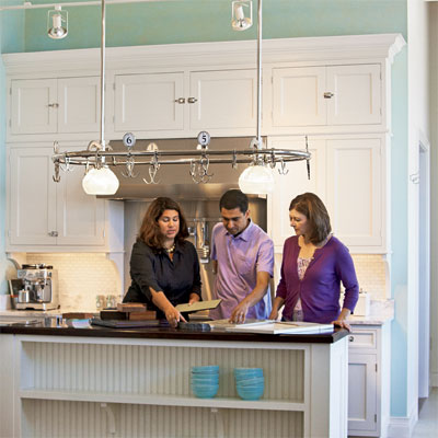 homeowners going over plans with kitchen designer at island