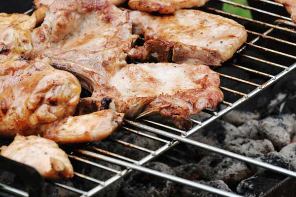 undercooked meat on a grill, ways barbecue can kill you