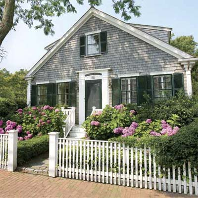 beautiful white picket fence before a house and flower garden