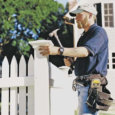 worker installing a cap on a fence post