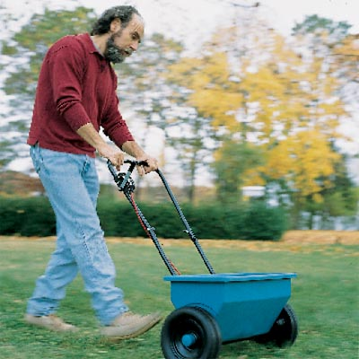 man spreading herbicides on lawn