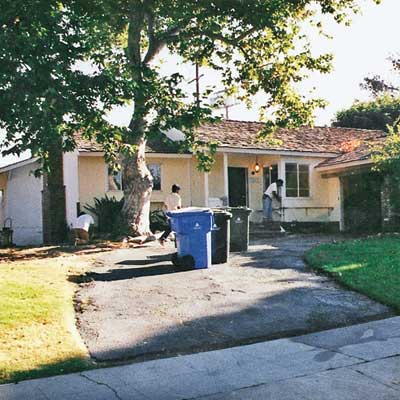 outdated house with sloped front yard before gardening remodel