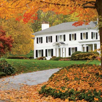 house nestled among brightly colored fall trees and shrubs