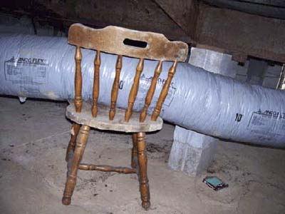 home inspection photo of chair supporting flex duct