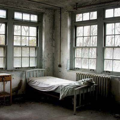 asylum room with bed in ruin of cottage