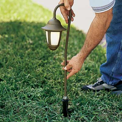 hands pushing a yard light fixture into the ground