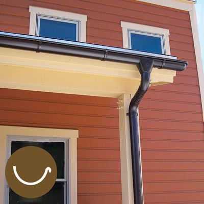 galvanized steel half-round gutter on a house with red siding