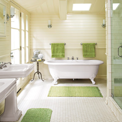 bathroom with clawfoot tub, hex tile, wainscoting, and green accents