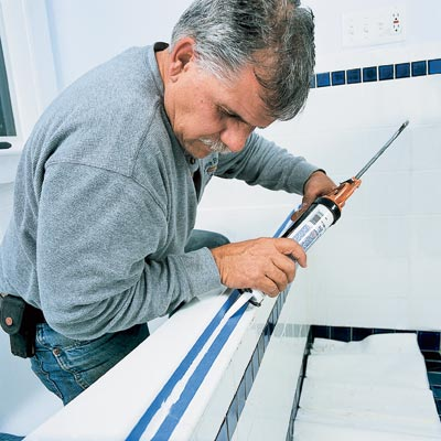 man using caulk on bathroom tub