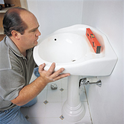 man replacing pedestal sink in bathroom