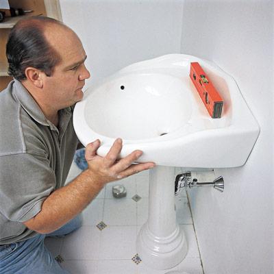 man replacing pedestal sink in bathroom