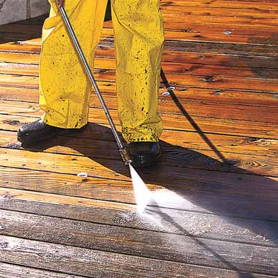 man powerwashing deck
