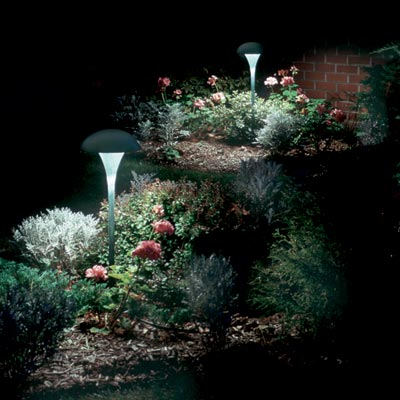 a flower bed illuminated by tulip-shaped outdoor lights