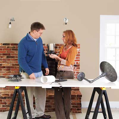 homeowner and lighting designer reviewing fixture options for efficient lighting