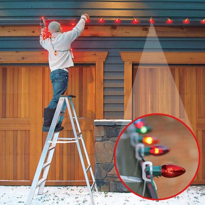 Man hanging christmas lights above garage