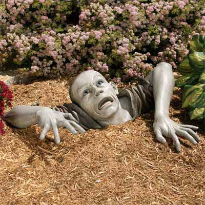 a zombie statue embedded in the earth for Halloween decor