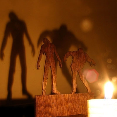a mahogany plywood Halloween decoration used to cast a shadow that looks like menacing zombies