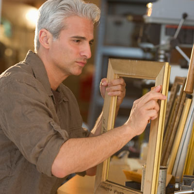 man inspecting joints of picture frame