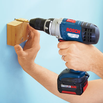 hands using drill driver to drill straight hole