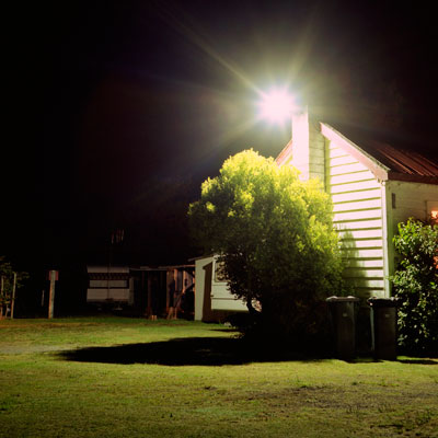house with flood light illuminating yard