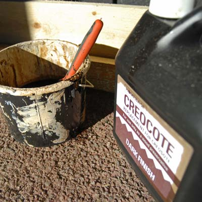 creosote container with brush and bucket