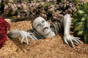 zombie yard sculpture sticking out of the ground in a flower garden