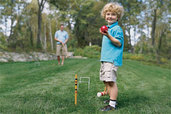 small child playing croquet in yard