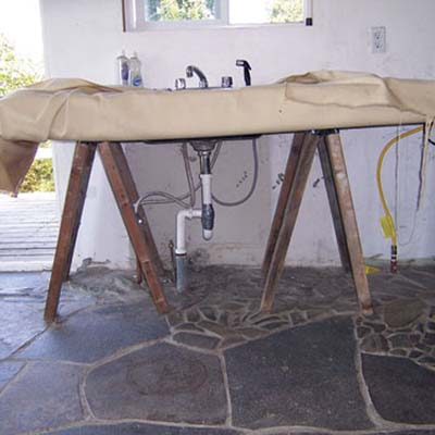 Kitchen made from sawhorses, plywood, pipes and tarp.
