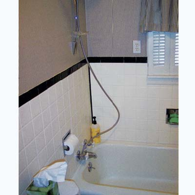 shower with an electrical outlet, window, and toilet paper holder