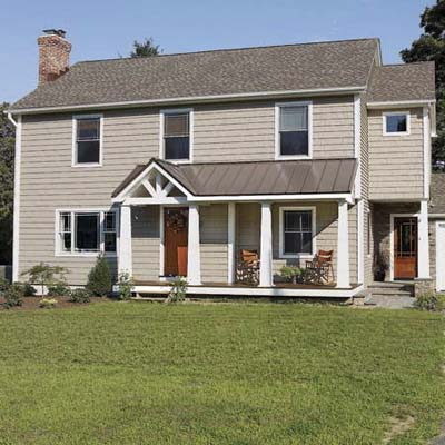 after exterior of Cape Cod remodel with added height to the roof, gables and front porch