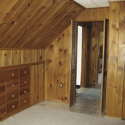 before photo of a knotty pine-paneled bedroom at Cape Cod remodel