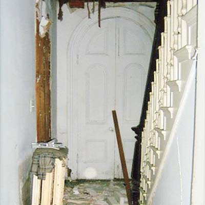 before photo of debris-strewn foyer with boarded up side entry