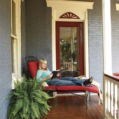 homeowner relaxing and reading a book on porch