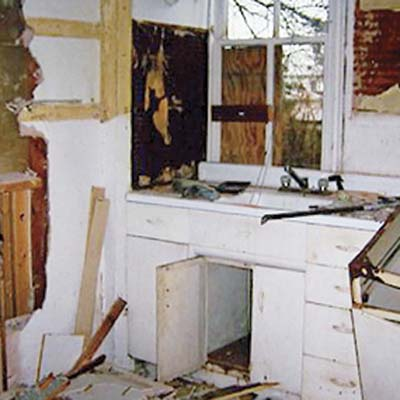 before photo of debris-filled kitchen with white metal cabinets