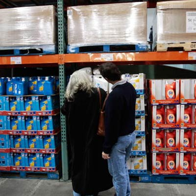 two shoppers looking at shelves of bulk items at a warehouse