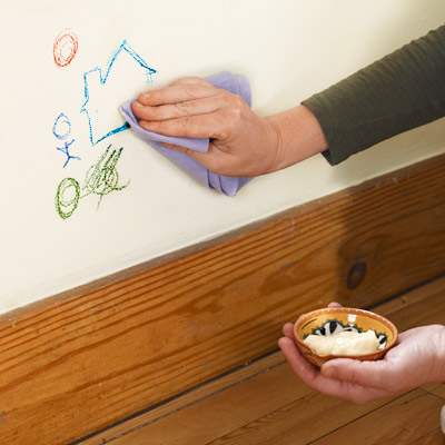 woman cleaning crayon drawing off wall with mayonnaise