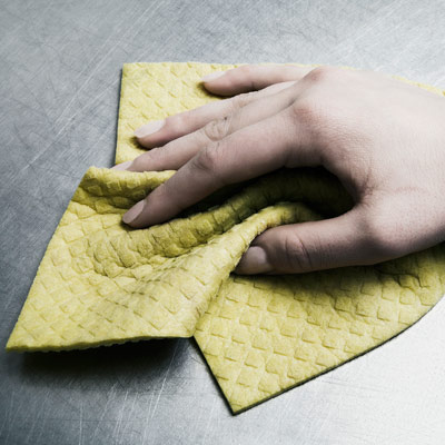 person cleaning a stainless steel surface