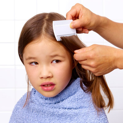 a woman combing a little girl's head for lice 