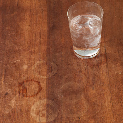 wood table with glass of water and water rings
